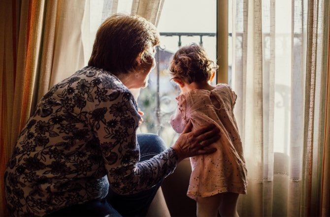 Grandmother looking out window with granddaughter